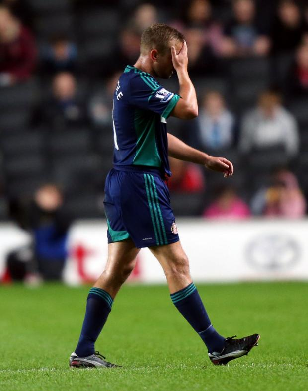 YET AGAIN: Lee Cattermole trudges from the field after being sent off during Sunderland's 2-0 win last night at MK Dons – the seventh red card of the 24-year-old's career