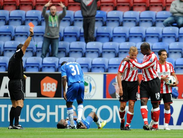 Sunderland's Lee Cattermole (centre) is sent off for a second bookable offence during a Premier League match at the DW Stadium, Wigan