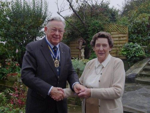 POPPY APPEAL: Connie Hewitson receiving a badge in recognition of her 60 years of poppy selling from Don Rutherford of the Royal British Legion.