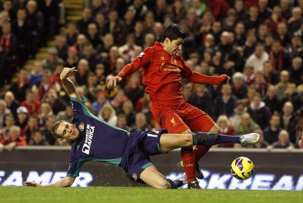 ON THE SLIDE: Sunderland's Matthew Kilgallon attempts to stop Liverpool's two-goal Luis Suarez during the Black Cats' 3-0 defeat last night