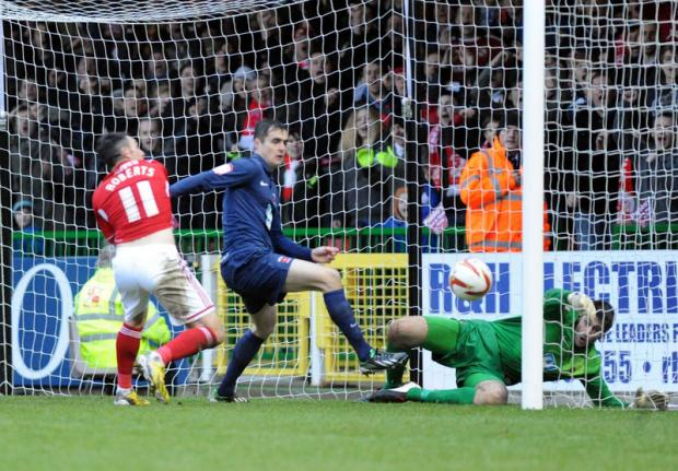 IN SUPERB FORM: Scott Flinders saves a point blank header from Adam Rooney, the first of three brilliant saves in a 90-second spell at Swindon