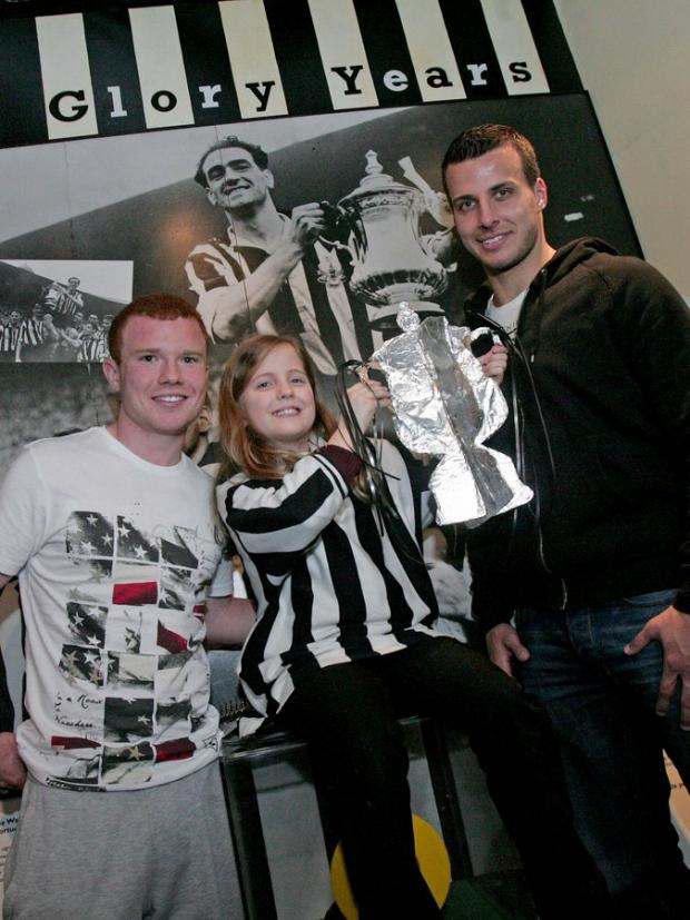 FOOTBALLING LESSON: Newcastle's Steven Taylor and Adam Campbell with with Yasmin Southell, ten, in front of a picture of Joe Harvey lifting the FA Cup for the Magpies in 1952. The Newcastle pair treated pupils from Benwell's Atkinson Road Primary Scho