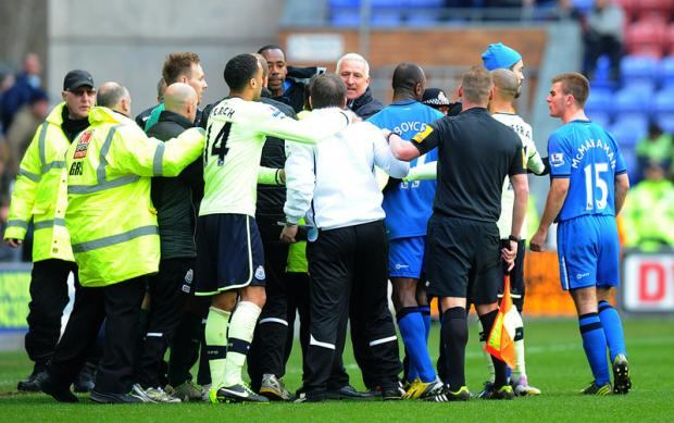 FLASHPOINT: John Carver, middle, wearing the white tracksuit top, is held back by James Perch, left, as Wigan coach Graham Barrow, in front of Carver, exchanges words with the Newcastle assistant manager while Callum McManaman, right, looks on.