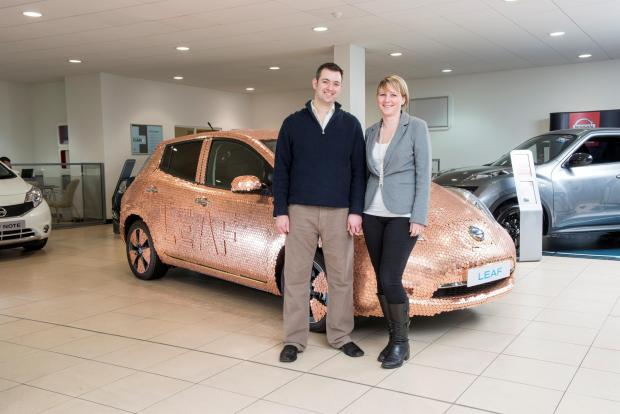 The Advertiser Series: Brett and Liz Garner in front of a Nissan leaf covered in coins