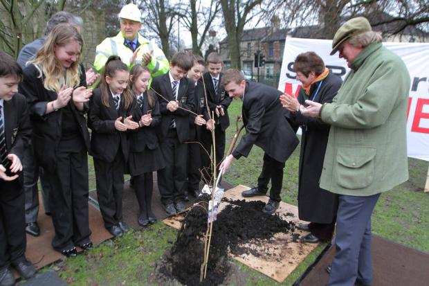 The Advertiser Series: Head Boy George Benson, 16, shovels earth into the planted tree at King James 1 Academy watched by children and ViPs at the ceremony