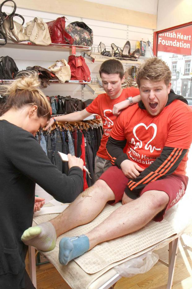 The Advertiser Series: Chris Gray feels the pain as he has his legs waxed by Sophie Muir at the British Heart Foundation shop in Northallerton, watched by Matty Burn, who also was waxed to raise money for the charity.
