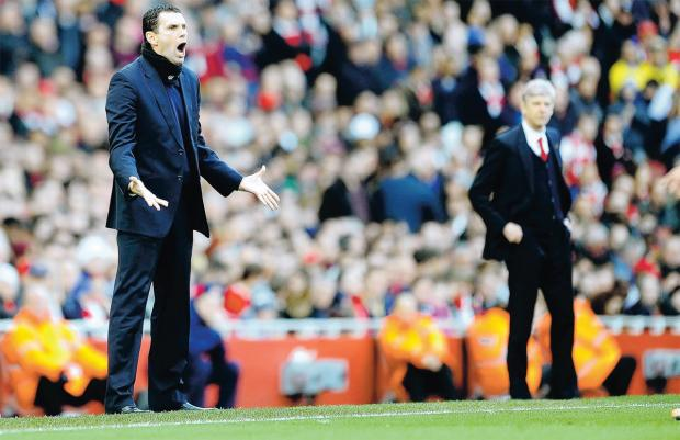 The Advertiser Series: TOUCHLINE TACTICS: Sunderland manager Gus Poyet, left, and Arsenal boss Arsene Wenger patrol their technical areas at the Emirates on Saturday