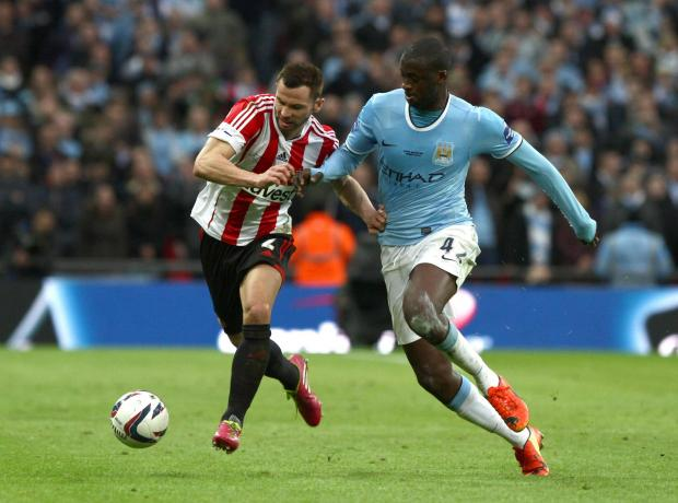 The Advertiser Series: TOURE TUSSLE: Phil Bardsley tries to shrug off the attentions of Yaya Toure