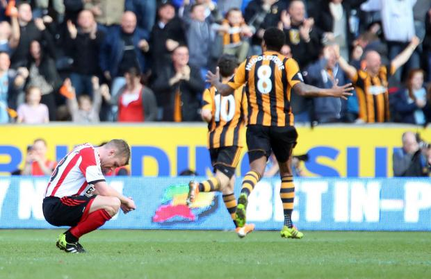 The Advertiser Series: EMOTIONAL MOMENT: As Hull players celebrate their third goal, Sunderland's Lee Cattermole drops to his knees after his mistake led to their goal