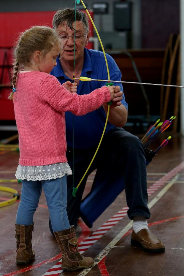 The Advertiser Series: HITTING THE TARGET: 4-year-old Hollie-Anne Sudder has a go during the archery taster day at Durham Free School with help from Colin Major from the St Giles' Archers. Picture: DAVID WOOD