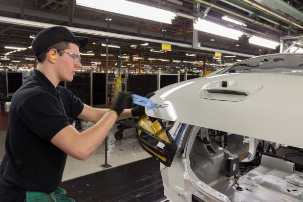 The Advertiser Series: PRODUCTION LINE: A Nissan worker peels off a sticker to reveal the Leaf badge on another of its electric vehicles at its North-East plant
