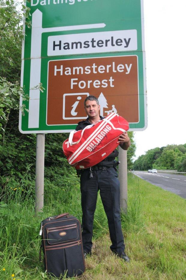 The Advertiser Series: DRUGS FIND: Sgt Dave Smith shows off his find next to the road sign where the bags had been dumped