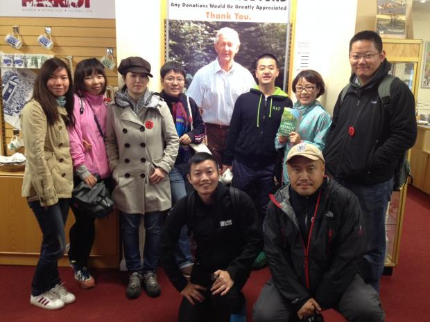 The Advertiser Series: HERRIOT FANS: The Chinese journalists gather by a image of the author.