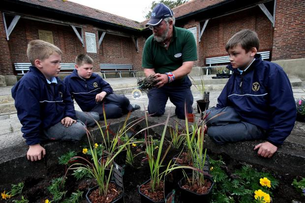 The Advertiser Series: COMMUNITY PROJECT: Pupils  Kori Gates (10), Callum  Hall (11) and Callum Benson from Burnhope Primary School work with Dave Errington, trainer assessor from Durham Agency Against Crime during the gardening project