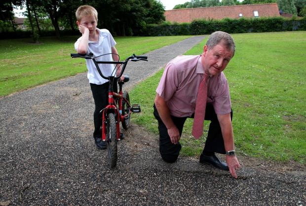 The Advertiser Series: TRACK FAULT: Headmaster Peter Wallbanks and disgruntled pupil Matthew Cain, 10, at the faulty cycle track at Walworth Special School, Newton Aycliffe