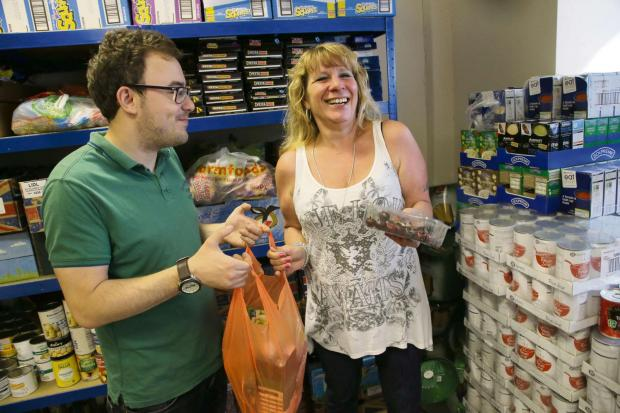 The Advertiser Series: FOODBANK: Karen Scott gets a food parcel from volunteer Ac Coltman at the foodbank at King's Church