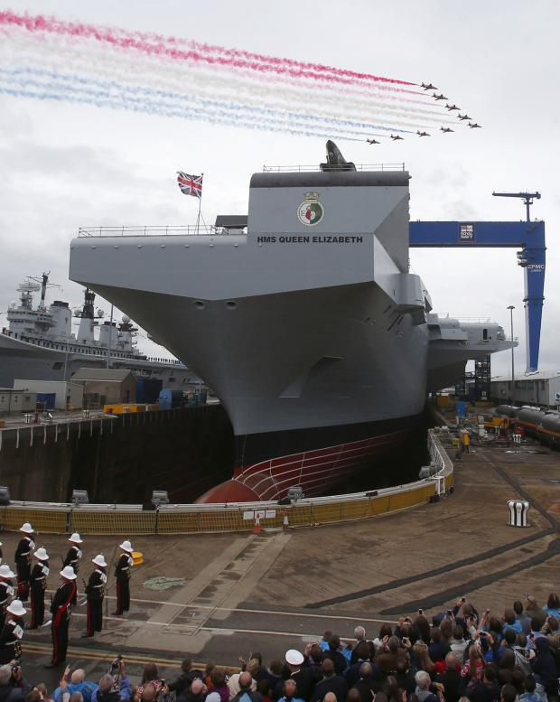 The Advertiser Series: COLOURFUL FLYOVER: The Red Arrows fly over as the Queen officially names the Royal Navy's new aircraft carrier HMS Queen Elizabeth during a visit to Rosyth dockyard in Scotland