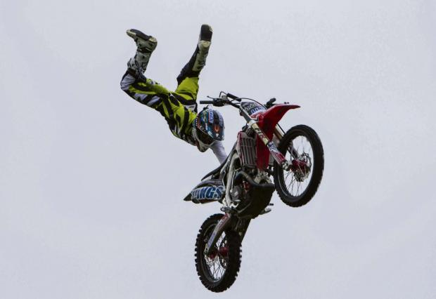The Advertiser Series: THE SHOW MUST GO ON: A stunt rider from the Bolddog Lings daredevil motorbike team soars across a grey sky at Great Aycliffe Show last year