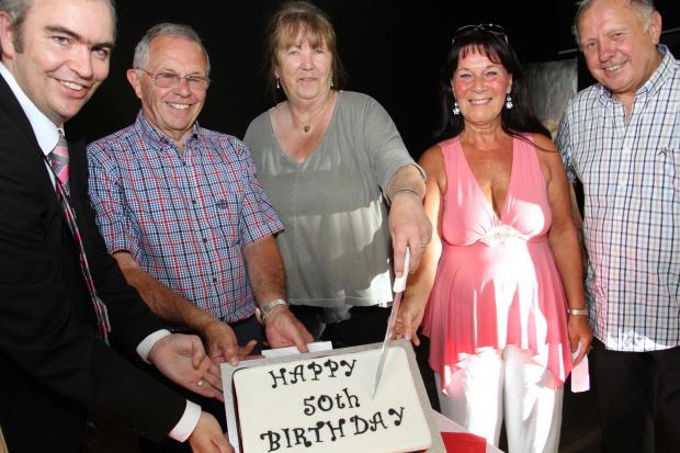 The Advertiser Series: GOLDEN MOMENT: DSMS head teacher Calvin Kipling, left, helps cut the 50th anniversary cake with former teachers Tony Forster, Linda Lindley, pupil of '64 Maria Rochester and retired art teacher Arthur Morgan