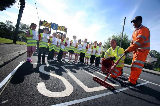 The Advertiser Series: Class One pupils with road marking operatives Mathew Toothill (kneeling)  and Terry Fox, of contractors