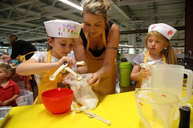 The Advertiser Series: LITTLE COOKS: Children prepare bread at the sessions at Tesco, Dragonville. From left Sophie Parks, six, Helen Farrow and Poppy Farrow, six.              Picture: ANDY LAMB (8779624)