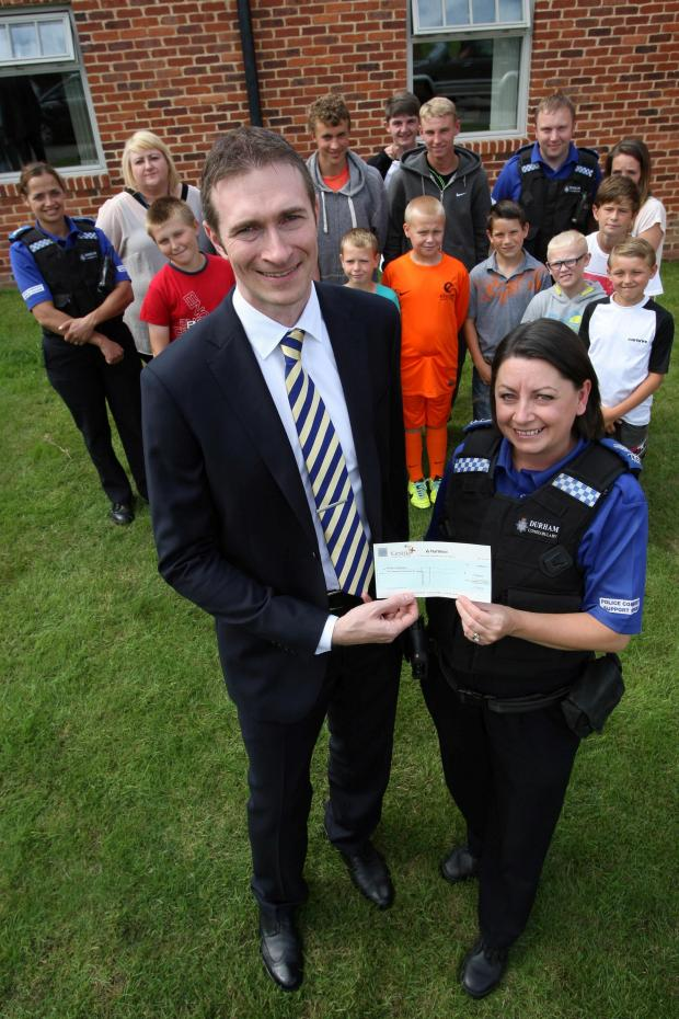 The Advertiser Series: COMMUNITY SPIRIT: Cestria Community Housing Director of Finance and Corporate Services, Martin Warhurst, hands a cheque over to PCSE Sonia Jameson for a football team set up by the police. Picture: TOM BANKS