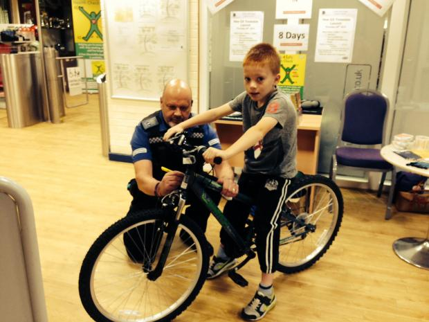 The Advertiser Series: BIKE MARKING: PCSO Michael Robson marks the bike of eight-year-old John Murphy