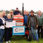 The Advertiser Series: PLOUGHING ON: Pam Ashmore (second from left) and Sue Birdsall (third from left) from the Teesdale branch of Cancer Research UK are presented with a cheque from a group of Swaledale farmers who staged two tractor runs over summer